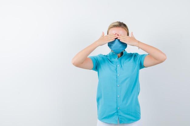 Giovane donna bionda in abiti casual, maschera che copre gli occhi con le mani e sembra confusa