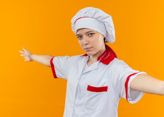 シェフの制服を着た若い金髪の女性シェフは、オレンジ色の壁で隔離の腕を開いて立っています