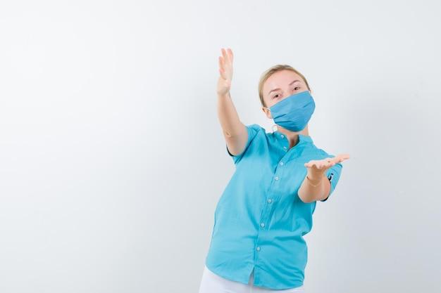 カジュアルな服装の若いブロンドの女性、マスクが来て陽気に見えるように誘う