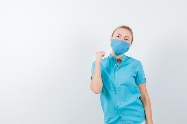 カジュアルな服装の若いブロンドの女性、親指で後ろを向いて物思いにふけるマスク
