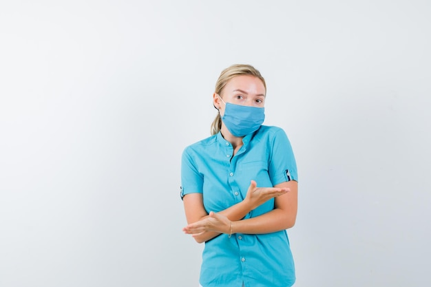 カジュアルな服装の若いブロンドの女性、交差した手で両側を示すマスク