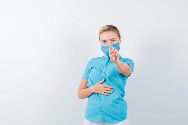 カジュアルな服装の若いブロンドの女性、微細なジェスチャーでホールドを示すマスク
