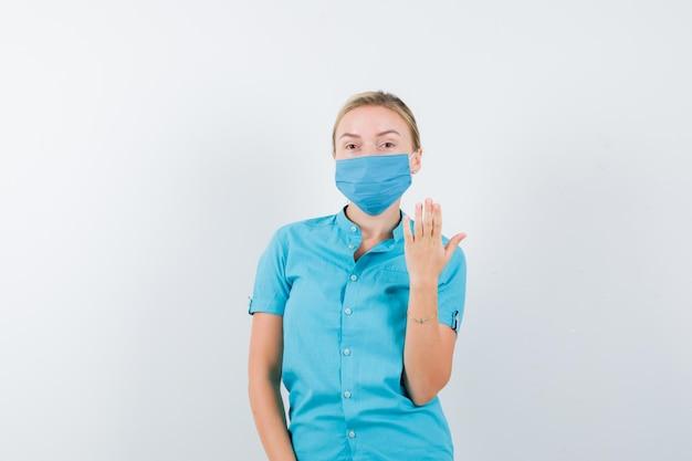 カジュアルな服装の若いブロンドの女性、爪を見せて暗い顔をしているマスク