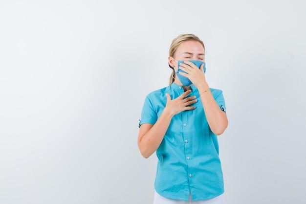 カジュアルな服装の若いブロンドの女性、咳に苦しんでいるマスクと痛みを伴う