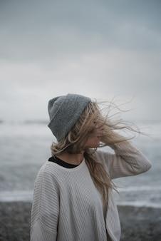 風の強い天気でビーチを歩く帽子とうつ病の若いブロンドの女性