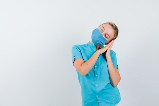 Giovane donna bionda che si appoggia sulle mani come cuscino in abiti casual, maschera e sembra assonnata