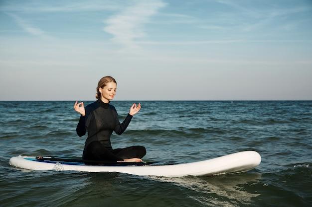 Молодая блондинка женщина на доске с веслом в море