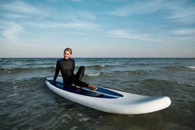 海でパドルボード上の若いブロンドの女性
