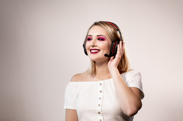 Young blonde female operator in headphones on light background. mock up