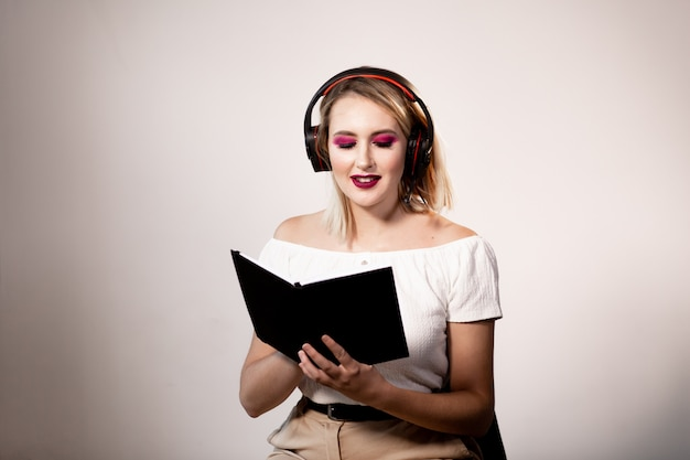 Young blonde female operator in headphones with notebook on light background. mock up