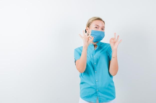 カジュアルな服装、マスク、陽気に見えるでokジェスチャーを示す若いブロンドの女性