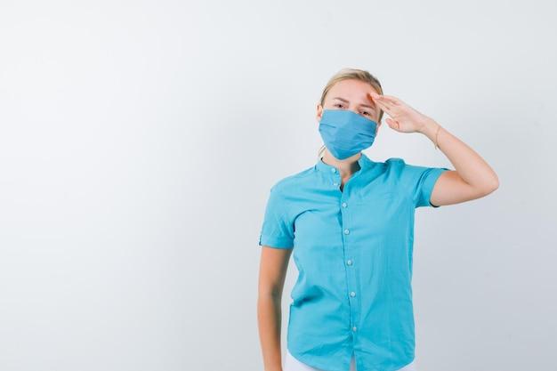 Giovane donna bionda che mostra gesto di saluto in abiti casual, maschera e sembra sicura
