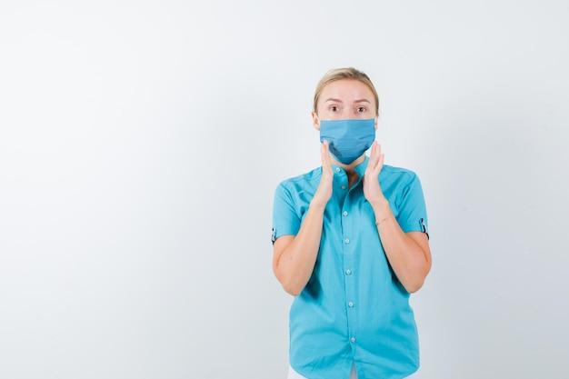 カジュアルな服装、マスク、自信を持って見えるサイズのサインを示す若いブロンドの女性
