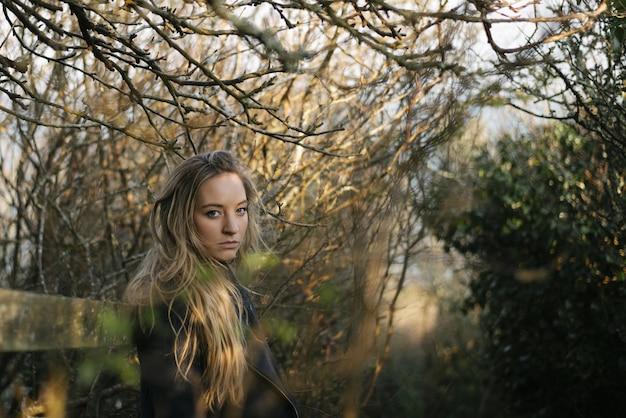 葉のない木々に囲まれた小道に立っている黒いコートを持つ若いブロンドの女性