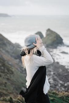 바람이 부는 날씨에 해변에서 재미 모자와 젊은 금발 여성