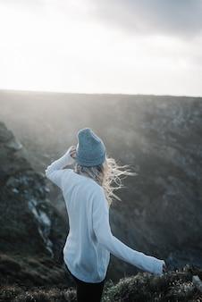 바람이 부는 날씨에 해변에 산책하는 모자와 젊은 금발 여성