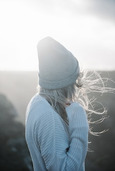 風の強い天気でビーチを歩く帽子をかぶった若いブロンドの女性