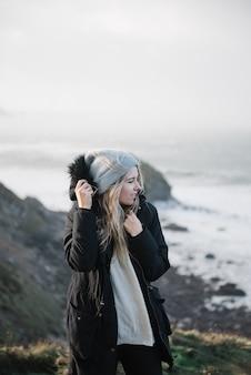 Giovane femmina bionda con un cappello che si diverte sulla spiaggia in un tempo ventoso