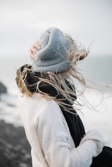 Giovane femmina bionda con un cappello che cammina su una costa rocciosa del mare in un tempo ventoso
