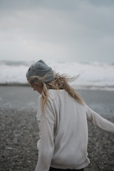 Young blonde female with a hat walking on a rocky sea coast in a windy weather