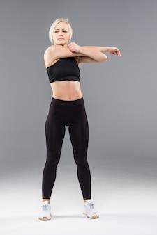 La giovane donna bionda adatta della ragazza sportiva in abiti sportivi neri dimostra il suo forte allungamento del corpo muscoloso