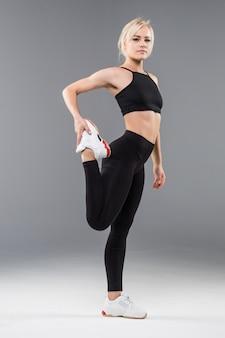 Молодая блондинка подтянутая спортивная девушка в черной спортивной одежде демонстрирует свое сильное мускулистое тело на растяжку