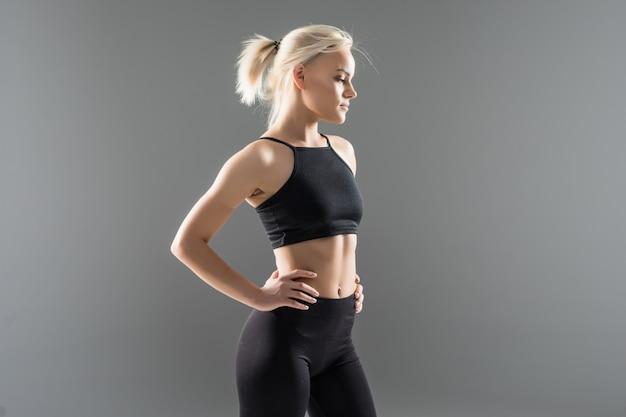 검은 운동복에 젊은 금발 맞는 스포티 한 여자 여자는 그녀의 강한 근육질 몸매를 보여줍니다
