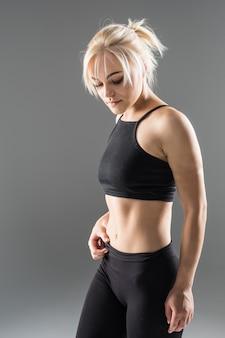 黒いスポーツウェアの若いブロンドフィットスポーティな女の子女性は彼女の強い筋肉ボディのストレッチを実証します