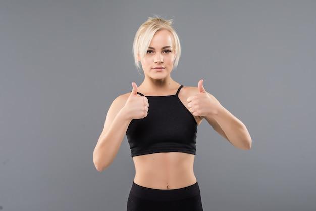 Молодая блондинка подтянутая спортивная девушка показывает палец вверх в черной спортивной одежде, демонстрируя свое сильное мускулистое тело