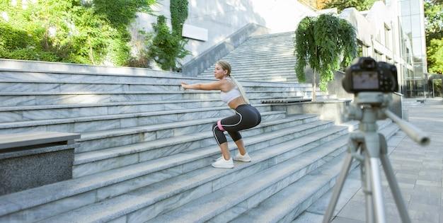 금발의 젊은 여성이 야외에서 피트니스 고무 밴드를 사용하여 계단에서 점프하는 연습을 하고 있으며 카메라에 블로그를 위한 비디오를 녹화하고 있습니다.
