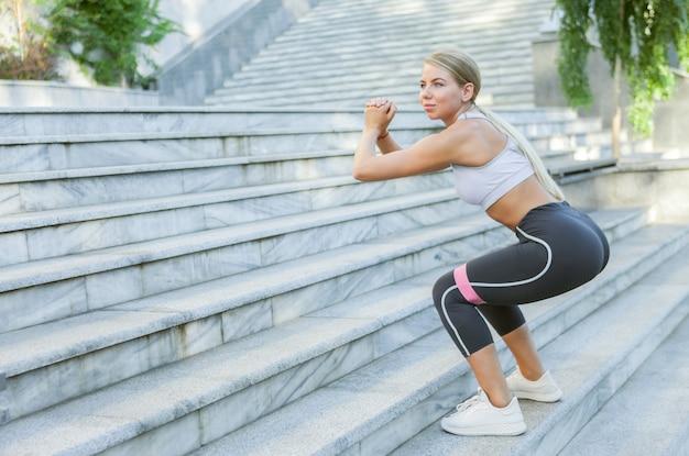 야외에서 피트 니스 고무 밴드와 함께 계단에서 점프를 연습 하는 젊은 금발의 맞는 여자