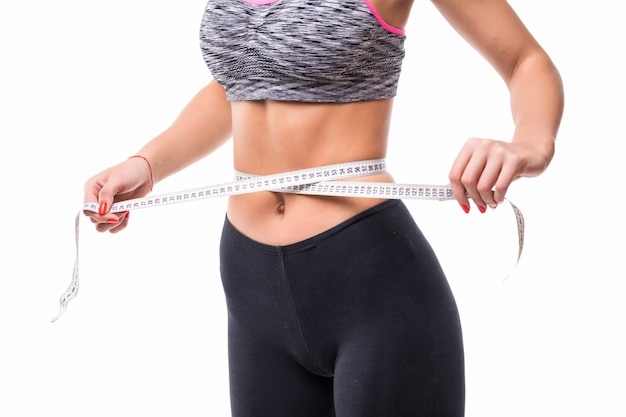 Young blonde fitness woman measuring her body with ruler dressed in fasion sportswear losing weight concept