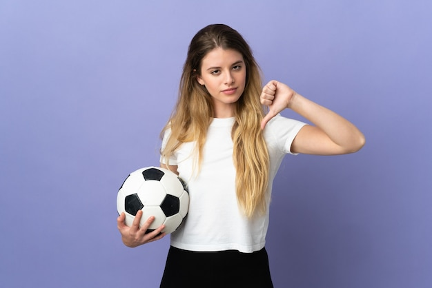 Young blonde football player woman isolated on purple wall showing thumb down with negative expression