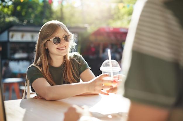 Молодая блондинка с веснушками покупает лимонад на ярмарке в солнечный жаркий летний день посреди городского парка.