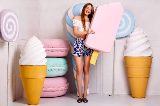 Молодая смешная блондинка позирует в студии возле гигантской сладости, держа в руках большое мороженое, миндальное печенье, кондитерскую, стильную летнюю одежду