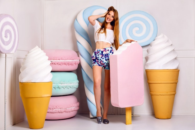 Young blonde funny woman posing in studio near giant sweetness, holding big ice-cream, macaroons