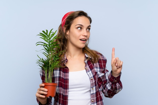 Young blonde gardener girl holding a plant intending to realizes the solution while lifting a finger up