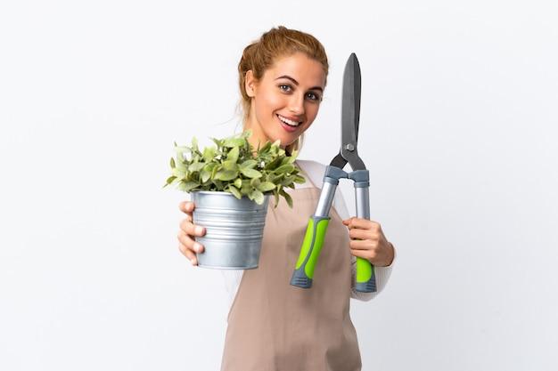 孤立した白い壁の上の若い金髪の庭師の女性