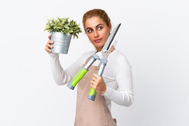 白い壁に若い金髪の庭師の女性