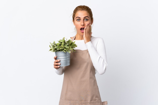 Young blonde gardener woman woman holding a plant over isolated white space with surprise facial expression