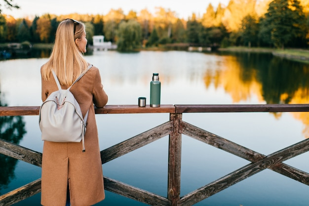 Молодая блондинка восхищается осенней природой пейзаж с пирса. одинокая взрослая самка пьет горячий чай из термоса в холодную погоду.