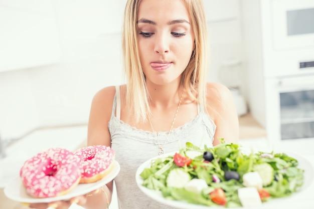 Молодая блондинка за завтраком или ужином на домашней кухне выбирает между пончиком и овощным салатом.