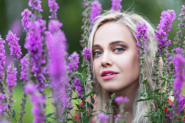 Young blonde girl in the bushes of purple flowers. close-up.
