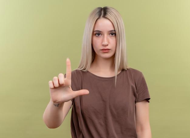Giovane ragazza bionda che fa il gesto della pistola che osserva sulla parete verde isolata