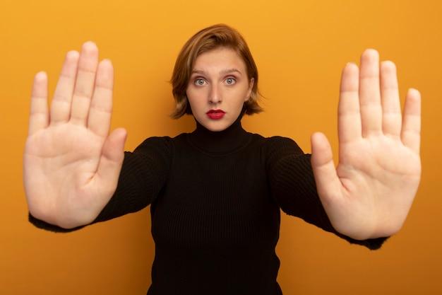 Молодая блондинка делает жест стоп, изолированные на оранжевой стене