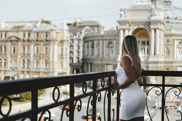 Young blonde girl dressed in white short dress in good shape is standing on the edge of the balcony and looking on the street with old architectural buildings