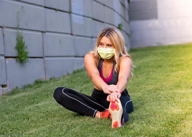 Covid-19 야외에서 의료 마스크 운동 젊은 금발 소녀