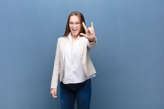 Молодая блондинка чувствует себя счастливой, веселой, уверенной, позитивной и мятежной, делая знак рок или хэви-метал рукой на бетонной стене