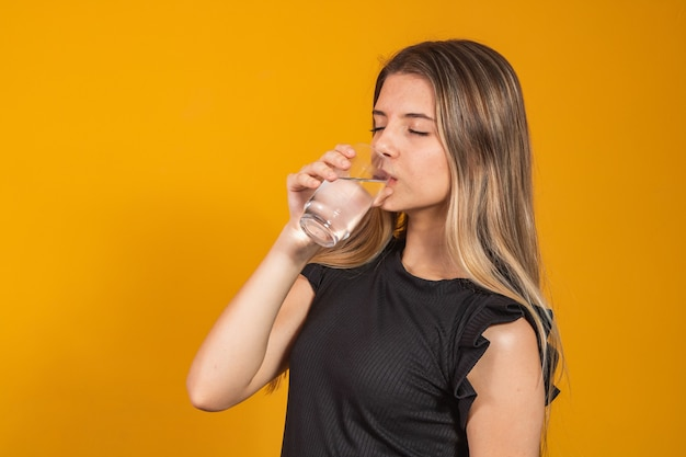 Young blonde girl getting hydrated drinking water