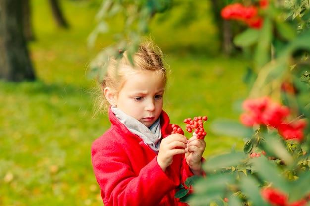 Молодая блондинка девушка держит в руках рябины